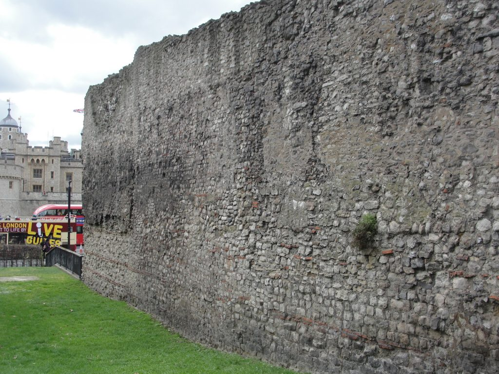 A stretch of the original (repaired) Roman wall of London. The Tower of London is in the distance.Ahead is the site of the Postern Gate, this being the start of the Roman wall.