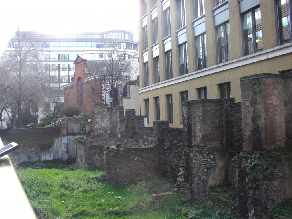 The stretch of the Roman wall of London (repaired/replaced) running alongside Noble Street. Also showing the church of St Anne and St Agnes.