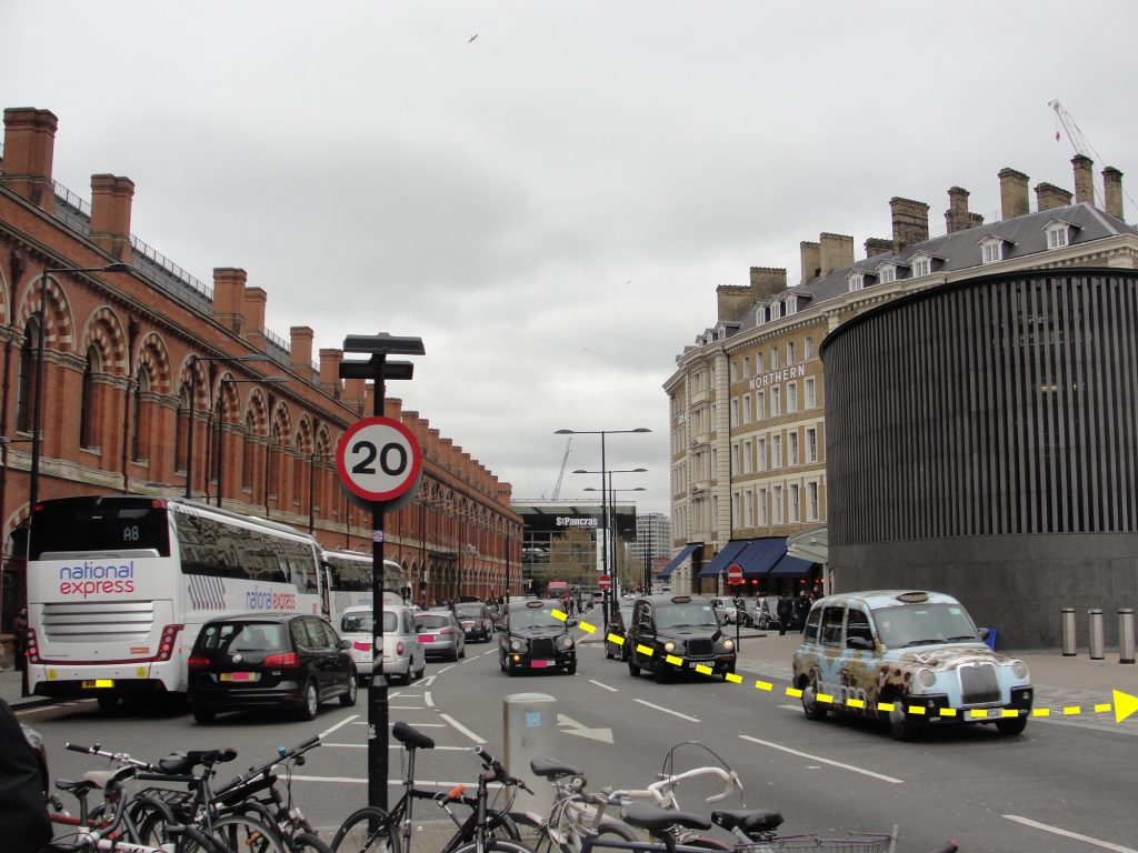 Looking north from Euston Road, London. St Pancras train station is on the left, King's Cross train station is out of shot on the right, and the Great Northern Hotel is visible on the right. An arrow shows the approximate former course of the River Fleet. The arrow follows the curve of the Great Northern Hotel.
